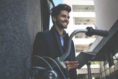 Hombre de negocios con la bici que se coloca en la calle y que sostiene el IP foto de archivo libre de regalías
