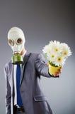 Hombre de negocios con la careta antigás y las flores Foto de archivo libre de regalías