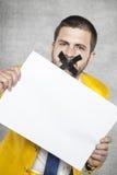 Hombre de negocios con la cinta en su boca, sosteniendo una tarjeta en blanco fotos de archivo libres de regalías