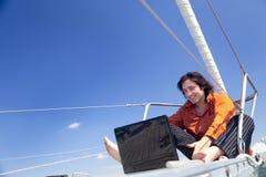 Hombre de negocios con la computadora portátil en el barco de vela Foto de archivo libre de regalías