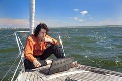 Hombre de negocios con la computadora portátil en el barco de vela Imágenes de archivo libres de regalías