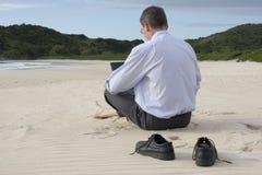 Hombre de negocios con la computadora portátil en la playa Imágenes de archivo libres de regalías