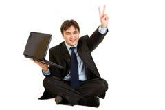 Hombre de negocios con la computadora portátil que muestra gesto de la victoria Imágenes de archivo libres de regalías