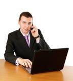 Hombre de negocios con la computadora portátil y el teléfono celular Imagen de archivo libre de regalías