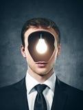 Hombre de negocios con la lámpara dentro de su cabeza en el gris fotos de archivo
