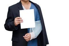 Hombre de negocios con la mano quebrada que lleva un apoyo del brazo y una tarjeta en blanco Fotos de archivo libres de regalías