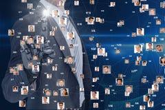 Hombre de negocios con la mano robótica que obra recíprocamente en la pantalla con los retratos del vuelo foto de archivo