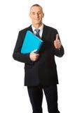 Hombre de negocios con la muestra aceptable que lleva a cabo una carpeta Fotografía de archivo