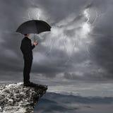 Hombre de negocios con la nube del temporal de lluvia de la mirada del paraguas Imágenes de archivo libres de regalías