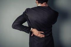 Hombre de negocios con la parte posterior dolorida y el cuello Fotos de archivo libres de regalías