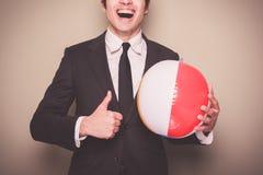 Hombre de negocios con la pelota de playa Fotografía de archivo libre de regalías