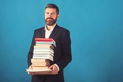 Hombre de negocios con la pila de libros en fondo azul Libro de la lección y de lectura de la literatura Tiempo de la escuela del fotos de archivo