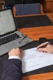 Hombre de negocios con la pluma, los documentos, el ordenador portátil y el smartphone Fotos de archivo libres de regalías