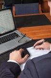 Hombre de negocios con la pluma, los documentos, el ordenador portátil y el smartphone Fotografía de archivo libre de regalías