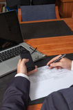 Hombre de negocios con la pluma, los documentos, el ordenador portátil y el smartphone Fotografía de archivo