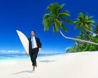 Hombre de negocios con la tabla hawaiana en la playa Fotos de archivo