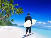 Hombre de negocios con la tabla hawaiana en la playa fotografía de archivo libre de regalías