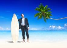 Hombre de negocios con la tabla hawaiana en la playa fotos de archivo libres de regalías