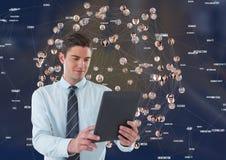 Hombre de negocios con la tableta contra ciudad de la noche con los conectores Imagenes de archivo