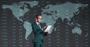 Hombre de negocios con la tableta del ordenador que se coloca sobre diagrama Mundo mA Fotos de archivo libres de regalías