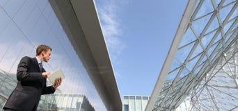 Hombre de negocios con la tableta que mira lejos en el cielo, en una escena del edificio urbano Foto de archivo libre de regalías