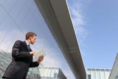 Hombre de negocios con la tableta que mira lejos en el cielo, en una escena del edificio urbano, computación de la nube Fotos de archivo libres de regalías