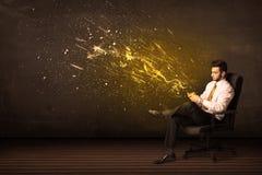Hombre de negocios con la tableta y explosión de la energía en fondo Foto de archivo libre de regalías