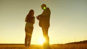 Hombre de negocios con la tableta y la mujer de negocios con la tableta discutir plan y horario en la puesta del sol y las risas  imágenes de archivo libres de regalías