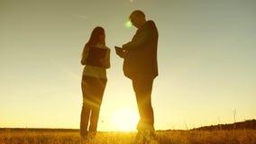 Hombre de negocios con la tableta y la mujer de negocios con la tableta discutir plan y horario en la puesta del sol y las risas  foto de archivo libre de regalías