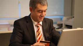 Hombre de negocios con la tarjeta de crédito, usando el ordenador portátil en oficina metrajes