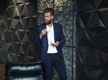 Hombre de negocios con la taza de café que localiza contra de fondo moderno foto de archivo