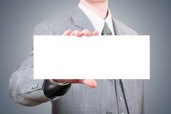 Hombre de negocios que muestra la tarjeta grande en blanco Imágenes de archivo libres de regalías