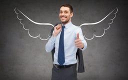 Hombre de negocios con las alas del ángel que muestran los pulgares para arriba imagen de archivo libre de regalías
