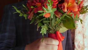 Hombre de negocios con las flores hermosas Ramo hermoso de rosas rojas en manos de hombres en chaqueta en un lazo y un blanco roj almacen de video
