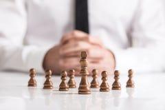 Hombre de negocios con las manos abrochadas que planean estrategia con ajedrez oscuro Fotos de archivo libres de regalías