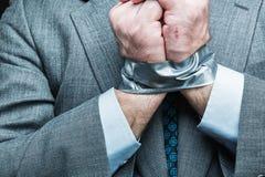 Hombre de negocios con las manos cubiertas por la cinta adhesiva Imágenes de archivo libres de regalías