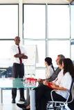 Hombre de negocios con los brazos plegables en una reunión Imagenes de archivo