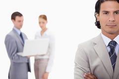 Hombre de negocios con los colegas con el ordenador portátil detrás de él Imágenes de archivo libres de regalías