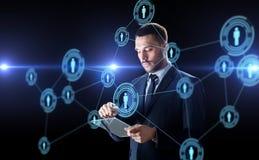 Hombre de negocios con los contactos de la PC y de la red de la tableta fotografía de archivo