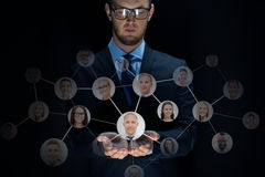Hombre de negocios con los contactos de la red sobre negro Imagenes de archivo