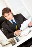 Hombre de negocios con los documentos que se sientan en el escritorio de oficina Imagenes de archivo