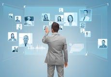 Hombre de negocios con los iconos de los contactos en la pantalla virtual Foto de archivo libre de regalías