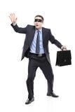 Hombre de negocios con los ojos vendados confuso con la cartera Foto de archivo