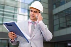 Hombre de negocios con los papeles que habla en el teléfono imagenes de archivo
