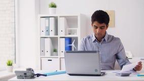 Hombre de negocios con los papeles que mecanografía en el ordenador portátil en la oficina
