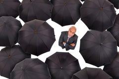 Hombre de negocios con los paraguas Imagenes de archivo