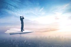 Hombre de negocios con los prismáticos en los aviones de papel Imágenes de archivo libres de regalías