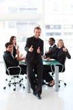 Hombre de negocios con los pulgares para arriba en una reunión foto de archivo