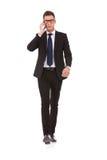 Hombre de negocios con los vidrios que habla en el teléfono móvil Fotografía de archivo