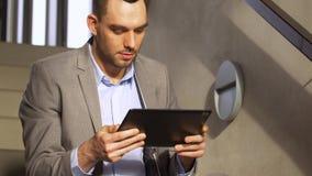 Hombre de negocios con PC de la tableta en las escaleras de la oficina metrajes